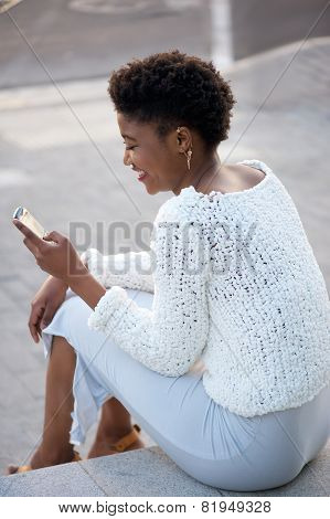 Happy Woman Sitting And Sending Text Message On Cellphone