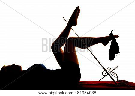 Silhouette Of Woman Lying Legs Up With Sword And Hat On Foot