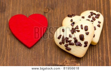 Biscuits and red little heart on wood