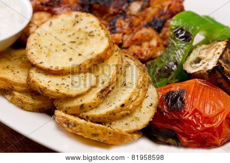 Grilled chicken fillets with potatoes and vegetables and mayo garlic dip