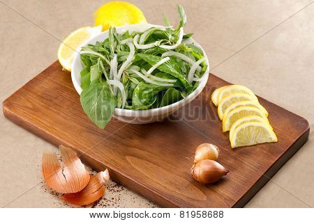 Rocket / Roquette / Arugula / Rucola salad leaves presented with ingredients on a wooden plate