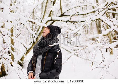 girl stares up in the winter forest