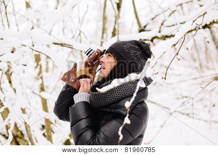 Girl photographs in winter forest