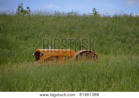 Old tractor hidden in long prairie grass