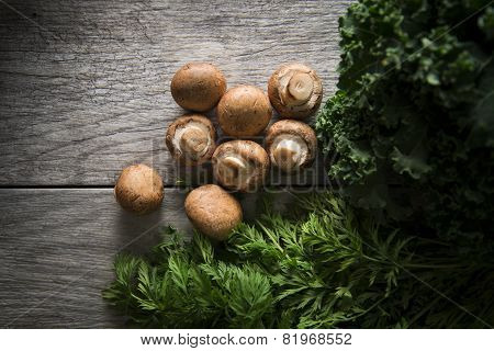 Mushrooms, carrot tops and kale on wood