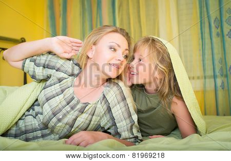 Mother and little daughter lying in bed and talking. Family. Bedtime.
