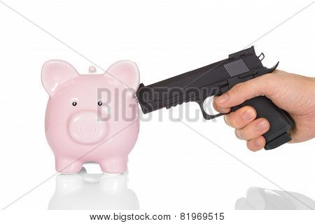 Hand With Gun Pointing At Piggy Bank