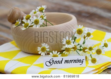 Good morning card with fresh chamomile flowers in wicker basket