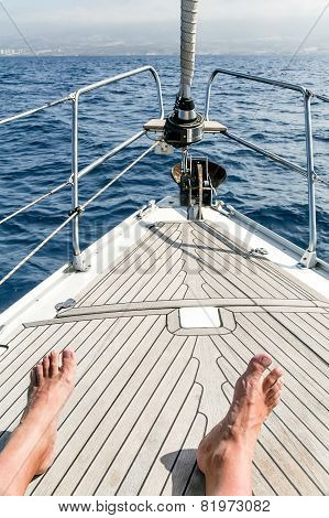 View of the legs of the photographer on the bow of the yacht
