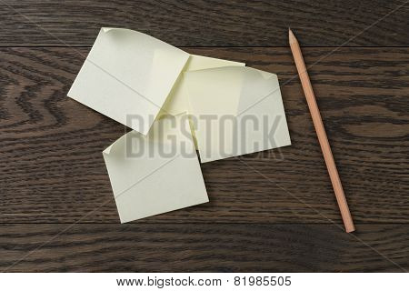 sticky note reminder on oak wood table with pencil