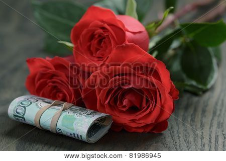 three red roses and bunch of russian money