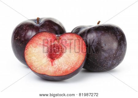 three ripe black plums isolated
