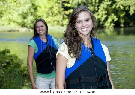 Two Outdoorsy Females With Life Jackets