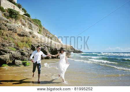 Happy Couple Holding Hands Running On The Beach Near Sea In Wedding Day