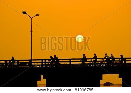 Men Riding Bicycles On The Bridge ,sunset