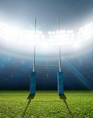 picture of illuminating  - A rugby stadium with rugby posts on a marked green grass pitch at night under illuminated floodlights - JPG