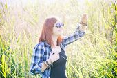 stock photo of tall grass  - Happy beautiful young woman on summer meadow in tall grass - JPG