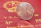 stock photo of yuan  - Chinese one yuan coin against the background of the Chinese passport