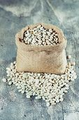 image of phaseolus  - Sack with white beans on wooden table - JPG