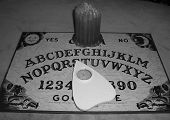 foto of ouija  - This is a Ouija board and candle in balck and white setting - JPG