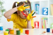 picture of finger-painting  - cute kid girl have fun painting her hands - JPG