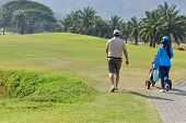 stock photo of caddy  - golf player and his caddy in the golf course - JPG