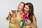 picture of two women taking cell phone  - Two girls friends with colorful clothing and makeup taking selfie with smartphone - JPG