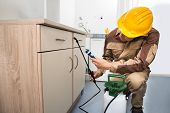 stock photo of pesticide  - Pest Control Worker Spraying Pesticides On Wooden Drawer - JPG