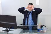 picture of suffering  - Portrait Of Businessman Suffering From Headache In Office - JPG
