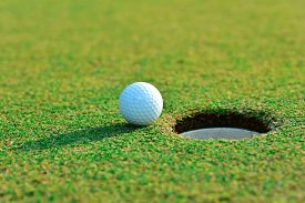 stock photo of caddy  - Close up of golf ball near the hole - JPG