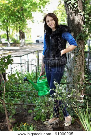 Woman In Gardening Waters Flowers
