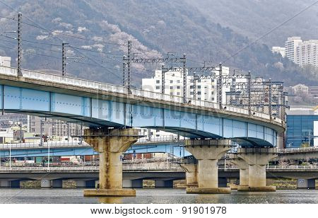 train bridge across river and city background at busan , korea