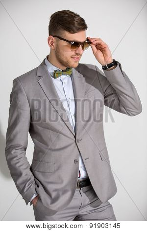 Attractive man in a suit and tie butterfly dress stylish sunglas