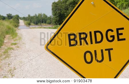 Bridge out -sign ahead of a flooding covered road warning drivers