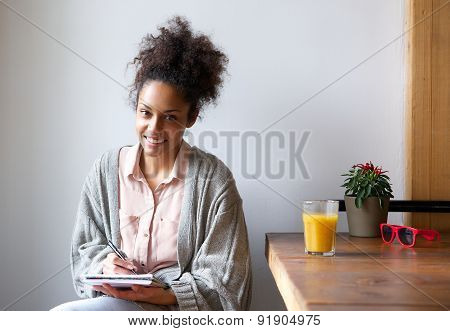 Smiling Young Woman Sitting At Home Writing In Note Pad