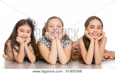 Three girls lying on the floor leaning