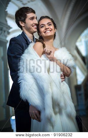 Portrait of happy wedding couple in classic interior