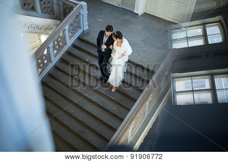 Fancy wedding couple holding hands walking the stairs down