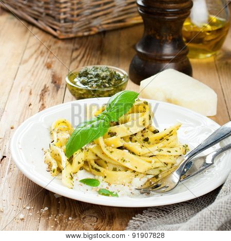 Pasta tagliatelle with pesto sauce and basil