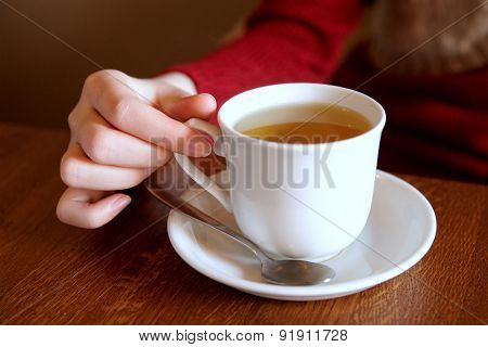 Human hand with a Cup of tea.