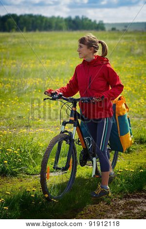 Portrait of the woman with loaded bicycle on the green meadow with flowers at sunny day