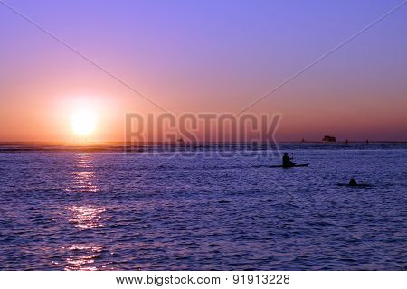 People And Boats In The Water During Sunset Over The Ocean
