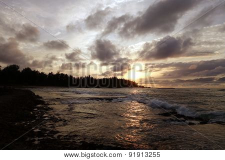 Sunset Through The Clouds And Over The Trees As It Reflects On The Watery Waves At Kawela Bay Rocky