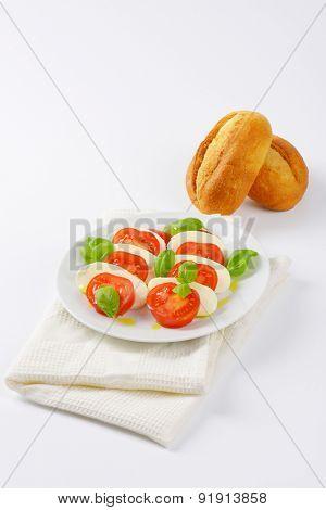 plate of caprese salad and fresh bun