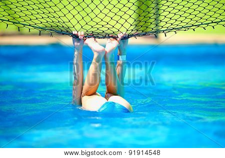 Cute Boy Kid Having Fun, Making Stunt On Volleyball Net In Pool