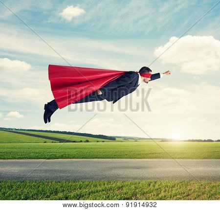 serious businessman dressed as a superhero in red mask and cloak flying at outdoor over beautiful landscape background
