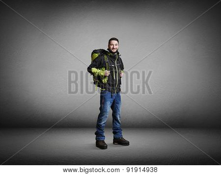happy tourist with backpacker smiling and looking at camera over grey background