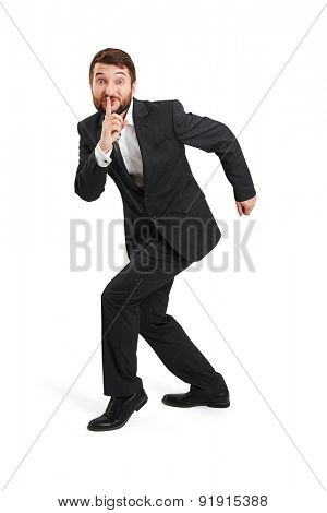 businessman in formal wear showing silent sign and walking on tiptoe. isolated on white background