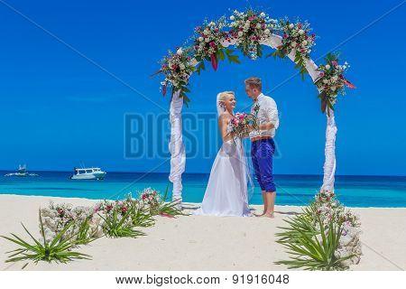 bride and groom enjoying beach wedding in tropics, on wedding arch, setup background