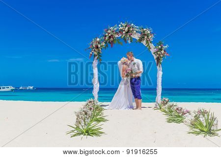 young loving couple, bride and groom, on their wedding day on wedding setup, arch, venue background, beach wedding in tropics